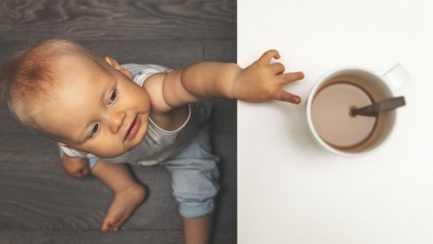 Baby reaching for a hot cup of tea