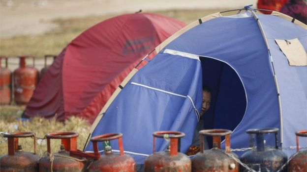 A Nepalese household looks on from her tent while waiting in a queue with their empty cooking gas cylinders for fresh supply in Kathmandu, Nepal, 18 November 2015.