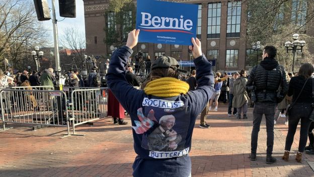 A woman at a Bernie rally holds up a sign