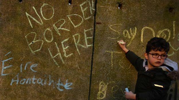 A boy writing anti-Brexit slogans on a wall on the Irish border