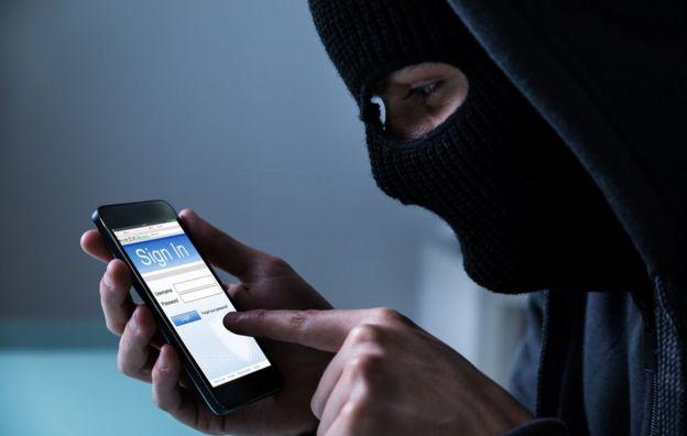 Hombre encapuchado se registra en una aplicación móvil.