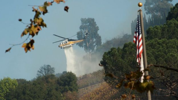 A helicopter drops water on a vineyard owned by Rupert Murdoch damaged by the Skirball fire near the Bel-Air neighbourhood on the west side of Los Angeles