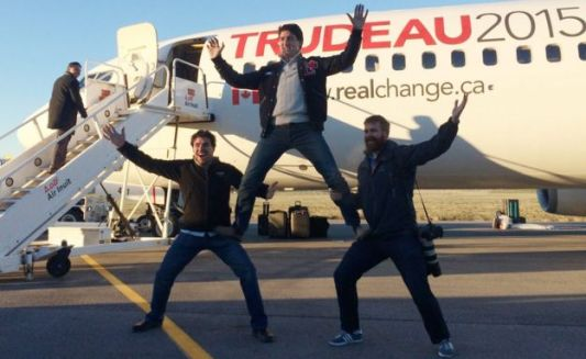 Canadian Liberal leader Justin Trudeau, center, clowns around with campaign team members Tommy Desfosses, left, and Adam Scotti after landing in Montreal, Monday, Oct. 19, 2015.