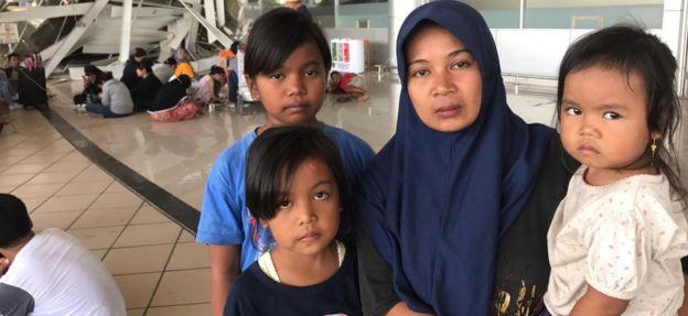 Wasliha and her three children at the airport