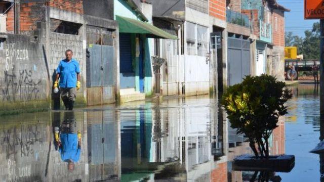 Homem usa galochas de borracha para atravessar rua inundada na periferia de São Paulo