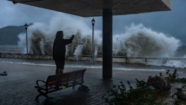 A man takes a photograph on the seafront in Hong Kong