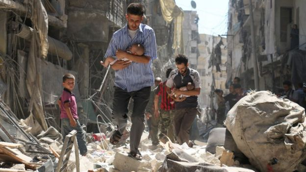 Syrian men carrying babies make their way through the rubble of destroyed buildings following a reported air strike on the rebel-held Salihin neighbourhood of the northern city of Aleppo, on 11 September 2016.