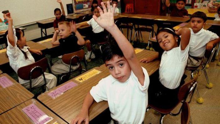 Varios niños levantan la mano en un aula escolar