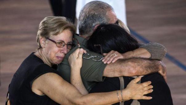 Familiares abrazados durante el funeral