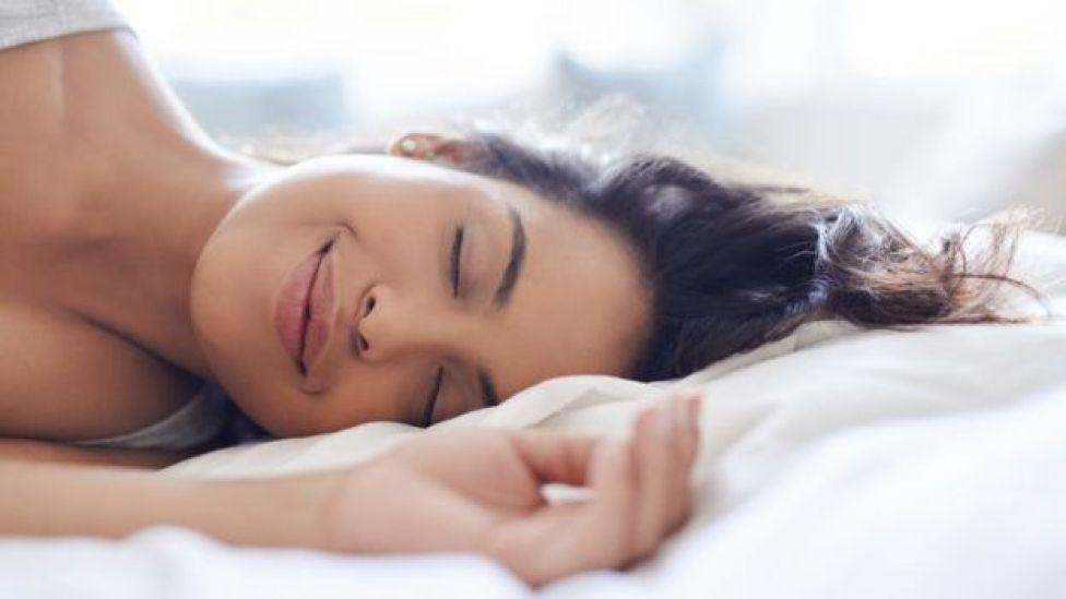 Une femme qui dort sur un lit en souriant