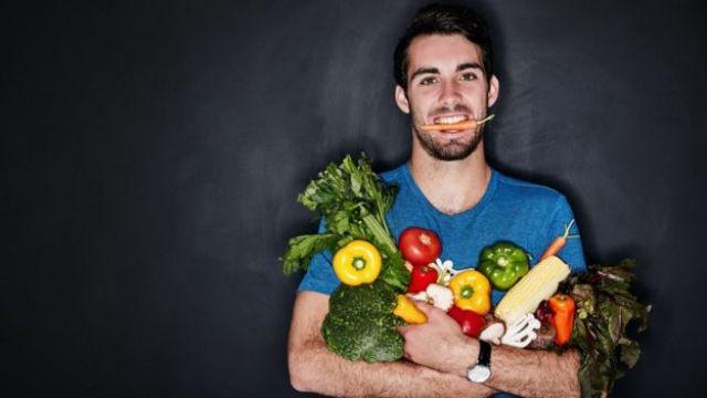 Homem carrega verduras e legumes