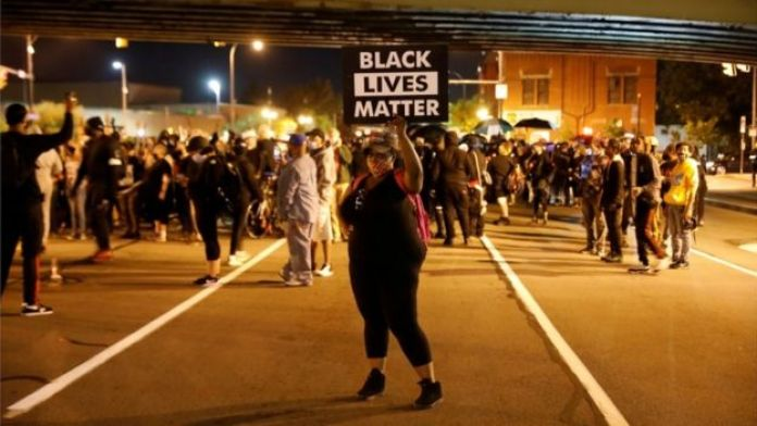"""A protester in Rochester, New York holds a sign saying """"Black Lives Matter"""""""