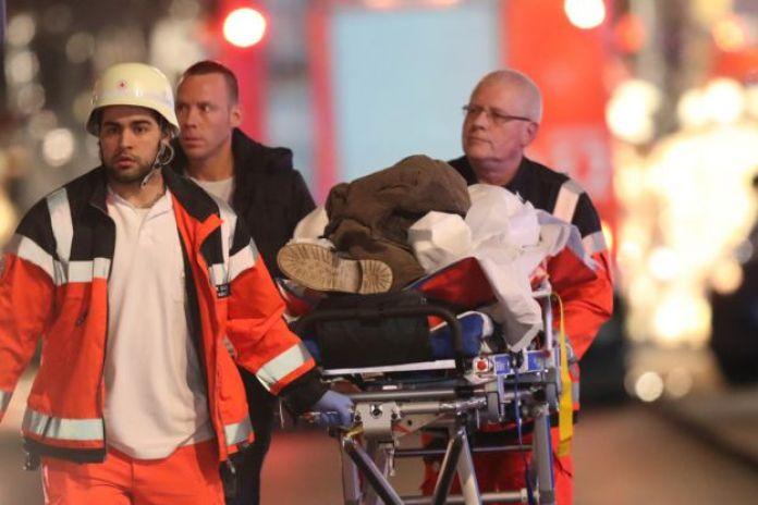 Yaralıları taşıyan acil yardım görevlileri