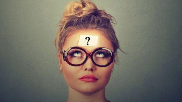 Mulher de óculos com um sinal de interrogação colado na testa