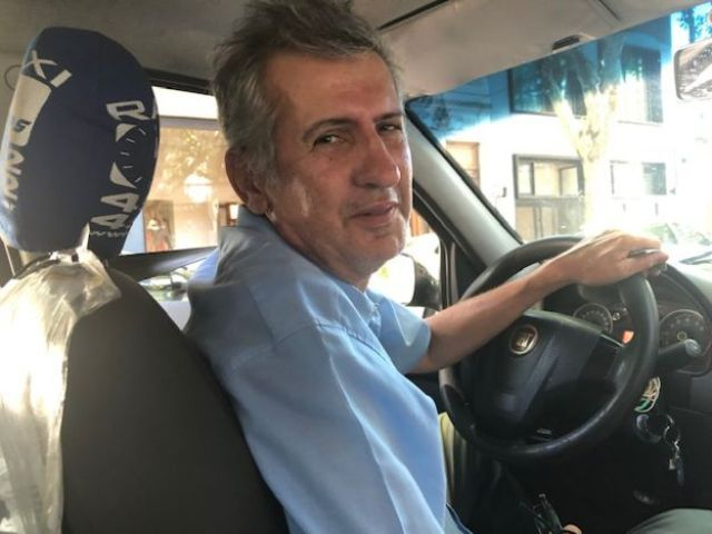 O taxista Marcelo Martínez posa para foto dentro do carro