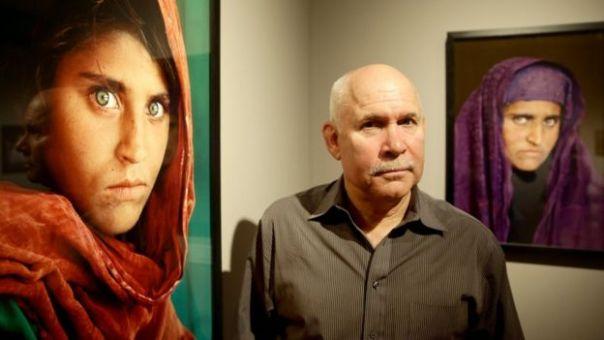 El fotógrafo Steve McCurry posa con las imágenes enmarcadas de Sharbat Gula, conocida como la