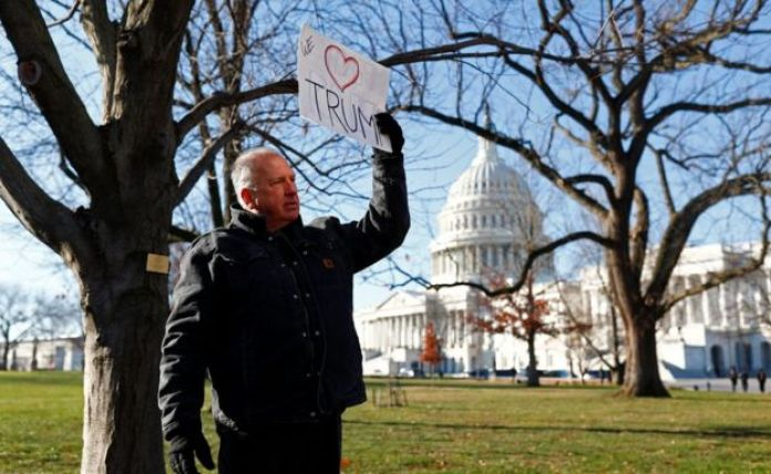 A man displays a pro-Trump sign near the Capitol on Wednesday