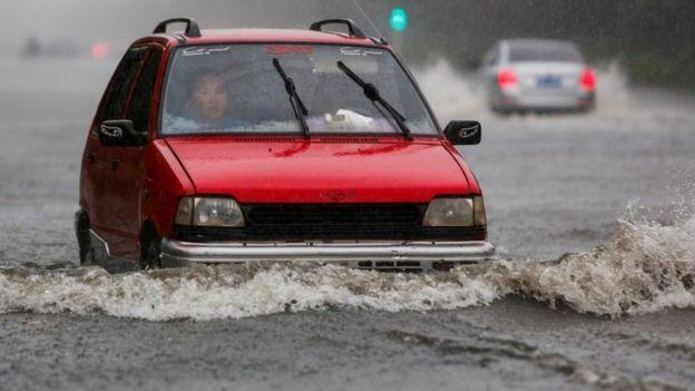 A car goes through a flooded street in rain, in Lianyungang, Jiangsu province, China June 23, 2016