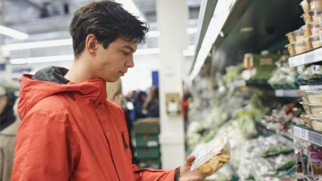 Joven eligiendo un producto en el supermercado.