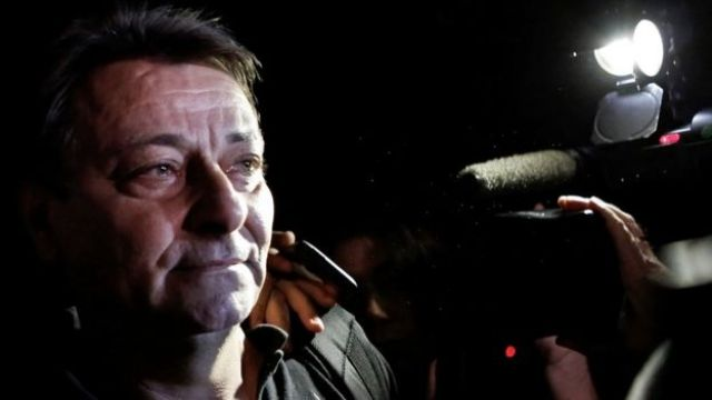 Em cena noturna, Battisti olha pro lado enquanto é cercado por câmeras em foto de 2015
