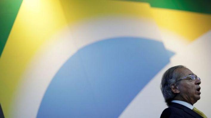 O ministro da Economia, Paulo Guedes, aparece de perfil com uma bandeira do Brasil impressa ao fundo