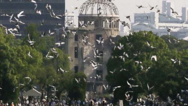 Doves fly over the Atomic Bomb Dome during the peace memorial ceremony marking the 70th anniversary of the atomic bombing at Hiroshima Peace Memorial Peace Park in Hiroshima (06 August 2015)