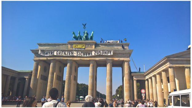 Anti-Islam activists have staged an hour-long demonstration atop Berlin's Brandenburg Gate Saturday 27 August 2016.