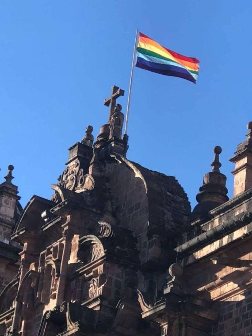 Bandeira do arco-íris de Cusco em fachada de igreja histórica