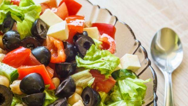 Prato de salada com tomate, zeitonas e outros vegetais