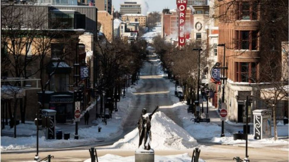 A sole individual walks down State Street in Madison, Wisconsin
