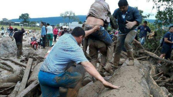 Personas entre los escombros dejados por el deslave,