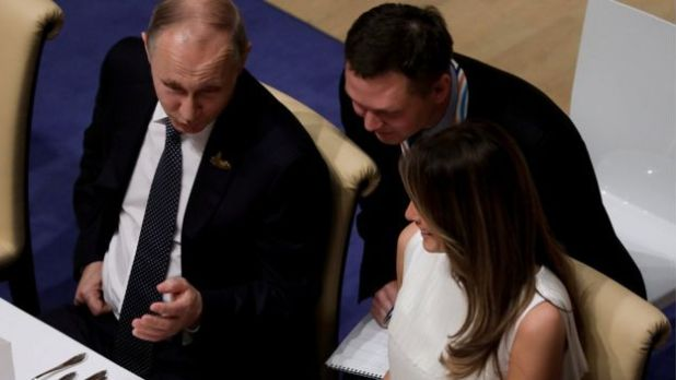 Russia's President Vladimir Putin talks to Melania Trump during the official dinner at the Elbphilharmonie Concert Hall during the G20 summit in Hamburg