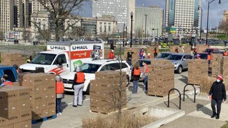 Fila de carros recebendo caixas com alimentos doados entregues por voluntários usando máscaras e coletes em cidade dos Estados Unidos