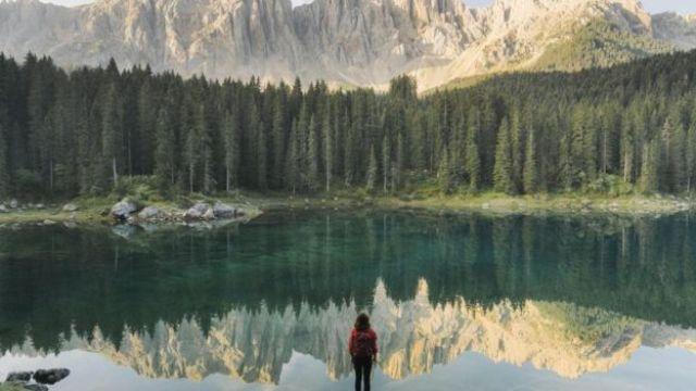Mulher diante de lago, floresta e montanha