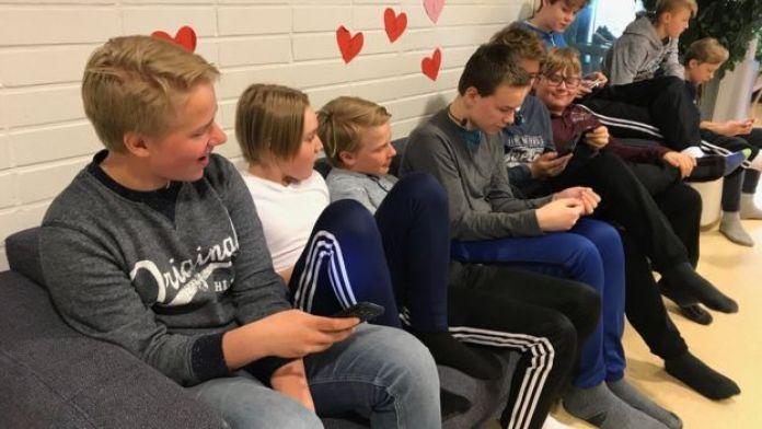 Niños a la hora de almuerzo utilizando su celular.