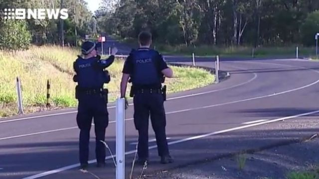 Two police officers stand at a roadblock in Queensland