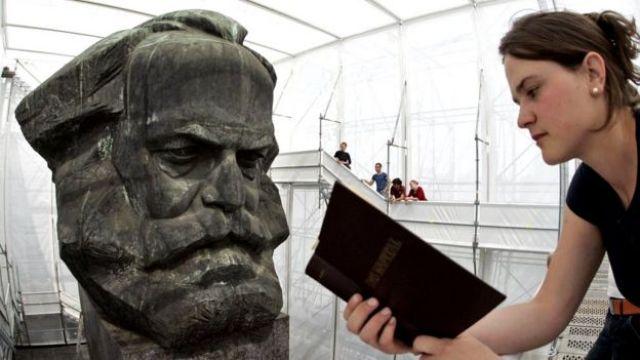 Jovem lee 'O Capital' em frente ao busto de Marx