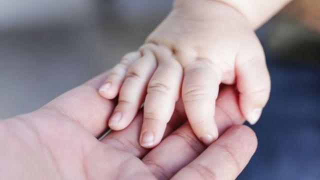 mão de mulher segurando a de bebê