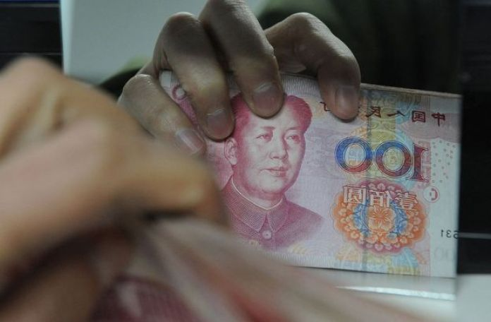 Chinese bank worker counts a stack of 100-yuan notes at a bank in Hefei, east China's Anhui province on 27 February 2011