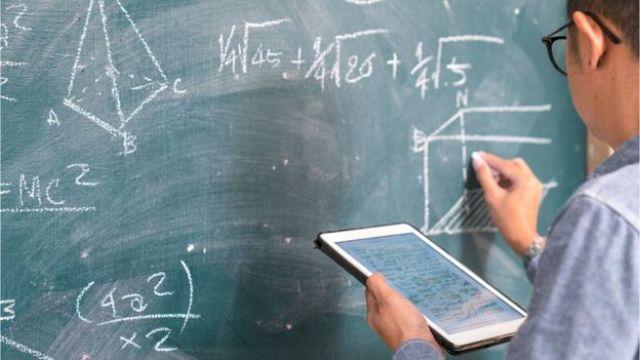Professor em lousa de matemática