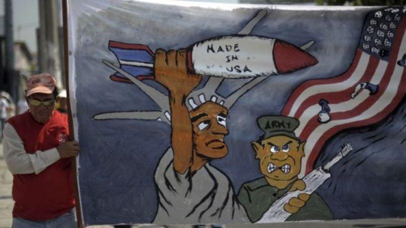"""Homem segura imagem com ilustração da estátua da liberdade segurando um míssil onde se lê """"feito nos EUA e de um soldado de El Salvador nas proximidades de uma bandeira americana; Manifestação lembrava em 2011 o assassinato do monsenhor Romero"""