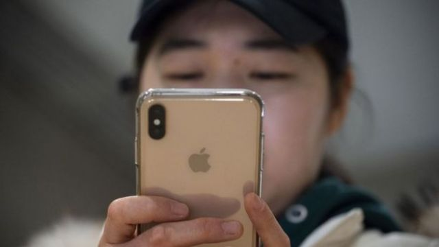Una mujer sostiene un iPhone.