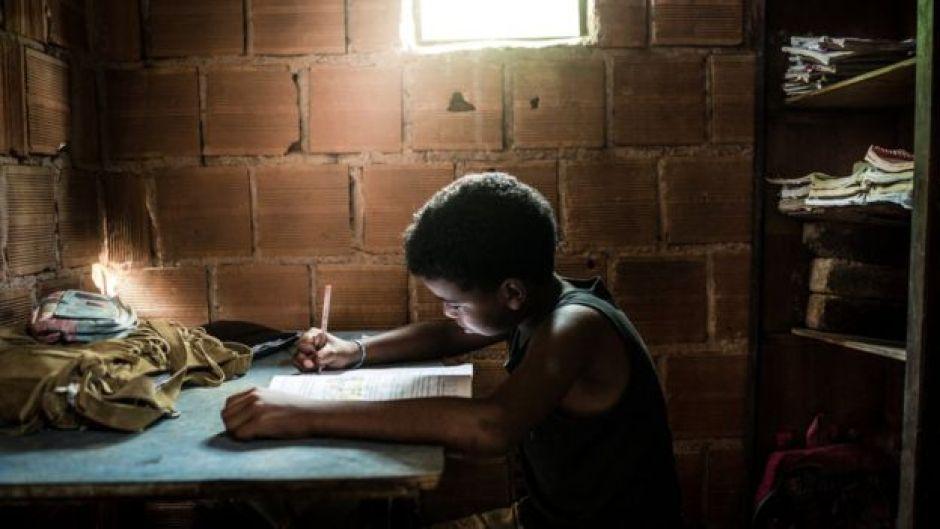 Menino estuda em uma casa precária