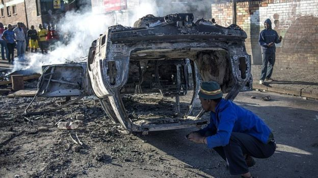 People look at a burnt-out car torched in the early hours outside the Jeppies Hostles, in the Jeppestown area of Johannesburg, on 17 April 2015