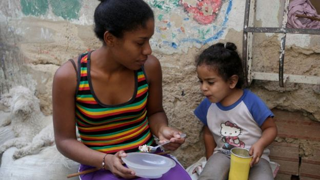 Mãe venezuelana alimentando a filha.