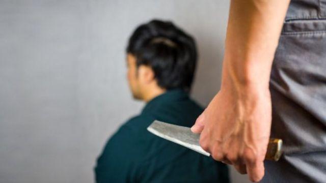 Hombre sosteniendo cuchillo frente a hombre organizado.