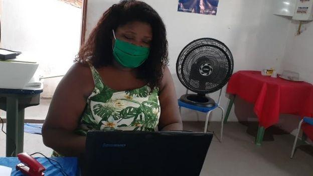 Christiane com máscara em frente a laptop em sala