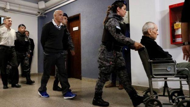 Nicola Corradi (right - in a wheelchair) Armando Gómez (centre) and Horacio Corbacho (left) leave the courtroom in Mendoza, Argentina. Photo: 25 November 2019