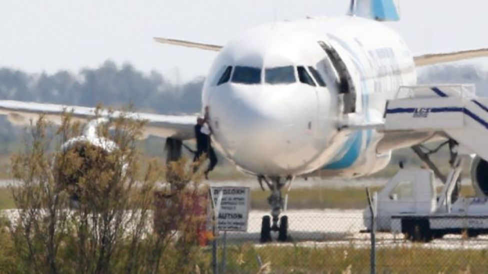 A man climbs out of the cockpit window an EgyptAir Airbus A-320 parked at the tarmac of Larnaca airport after being hijacked and diverted to Cyprus on 29 March 2016