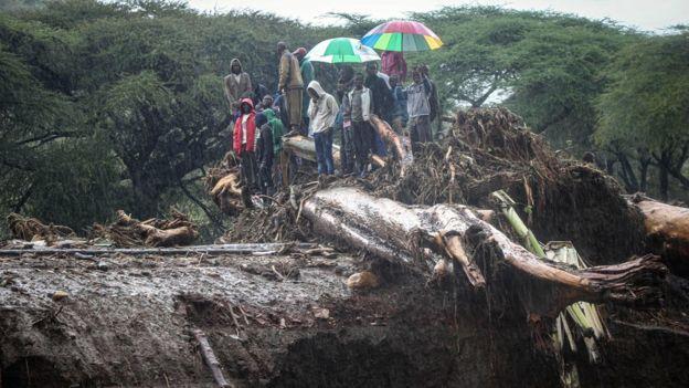 أشخاص يقفون على أنقاض يسدون طريقًا سريعًا على جسر بعد أن انفجر نهر موروني على ضفافه في غرب بوكو ، كينيا - نوفمبر 2019
